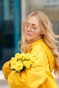 Blonde aux fleurs jaunes sur fond bleu lors d'une promenade en ville
