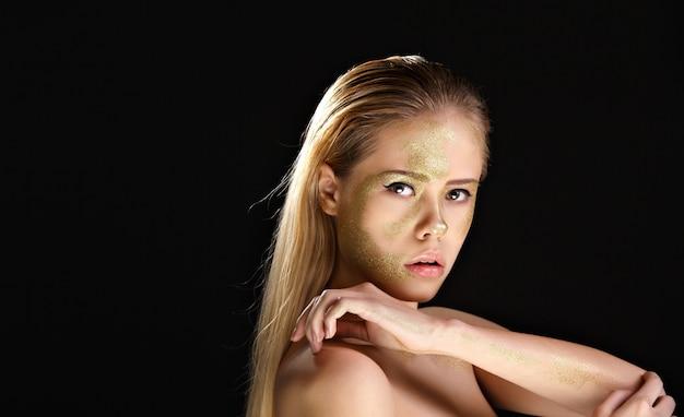 Blonde aux seins nus avec maquillage doré