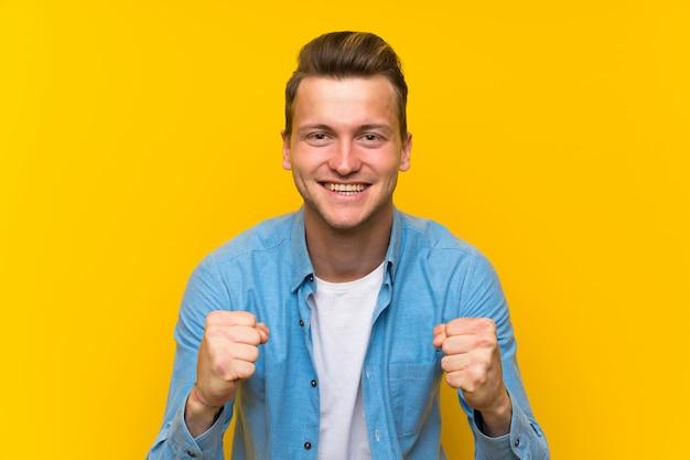Blonde bel homme sur un mur isolé célébrant une victoire