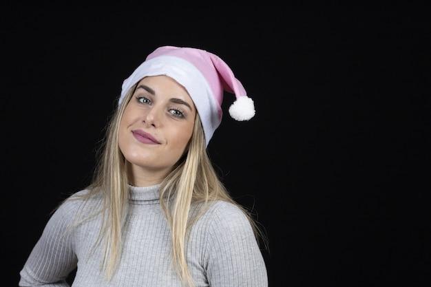 Blonde belle femme avec un chapeau de père noël rose posant sur un mur noir