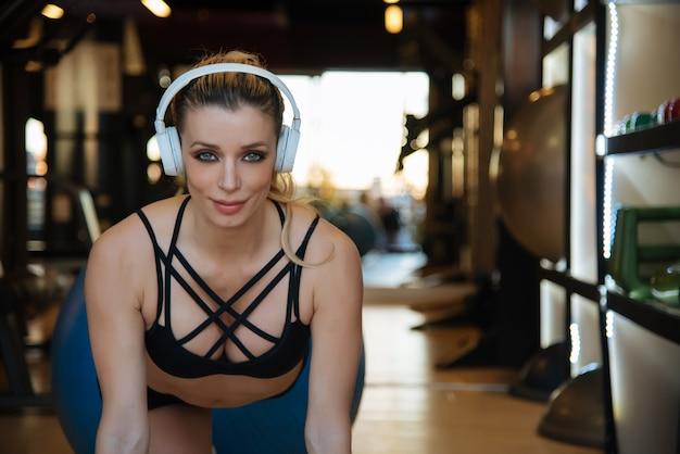 Blonde belle femme s'entraînant dans la salle de gym écouter de la musique