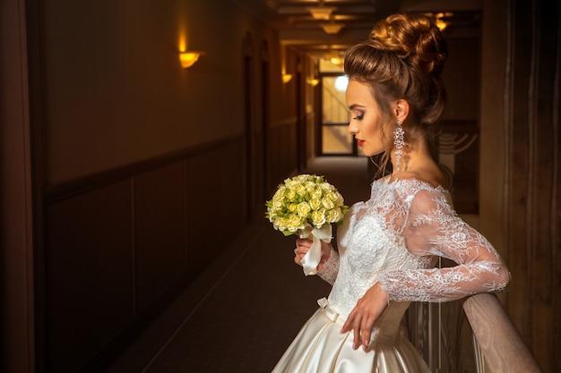 Blonde belle mariée en robe de mariée à la mode avec bouquet de roses dans les mains