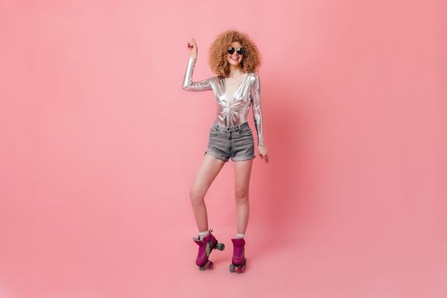 Blonde bouclée à lunettes rit et danse. femme en chemisier argenté et short pose sur des rouleaux en studio rose.