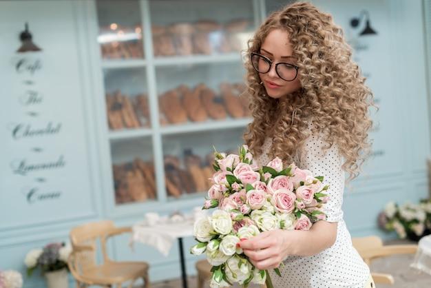 Blonde boucles fille dans les verres avec bouquet de roses