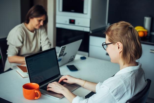 Blonde et brune travaillent sur des ordinateurs portables, assises à une table dans la cuisine face à face. coworking dans un intérieur confortable.