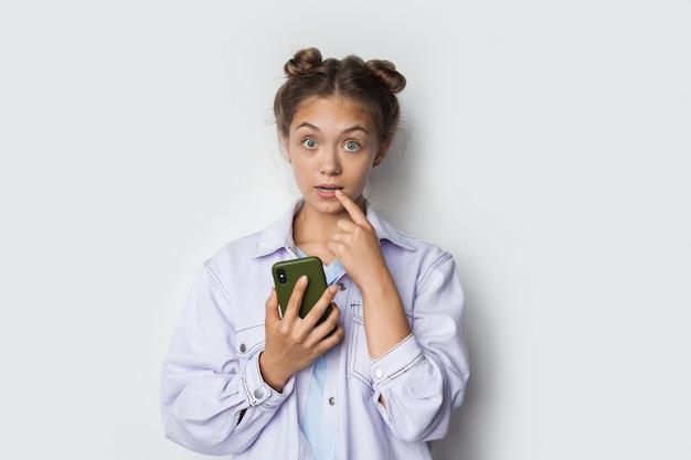 Blonde caucasian lady fait des gestes surprise sur un mur de studio blanc en tenant un téléphone et en regardant la caméra