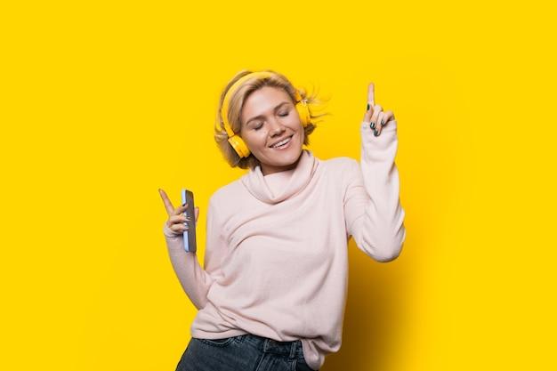 Blonde caucasian woman dancing sur un mur jaune tout en écoutant de la musique
