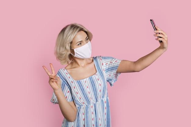 Blonde caucasian woman making a selfie gestes le signe de paix portant un masque médical sur le visage sur un mur de studio rose