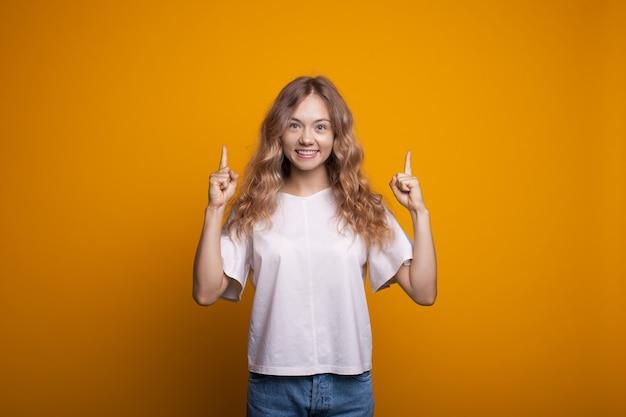 Blonde caucasian woman publicité quelque chose de souriant à la caméra sur un mur jaune pointant vers le haut avec l'index