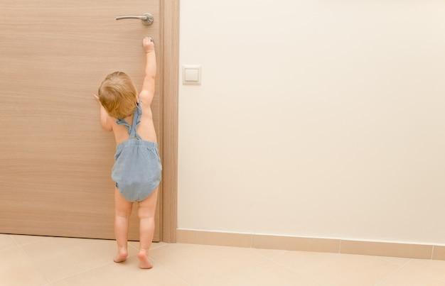 Blonde caucasienne petite fille de 12 ans essayant d'ouvrir la porte idée de sécurité des enfantscopier l'espace