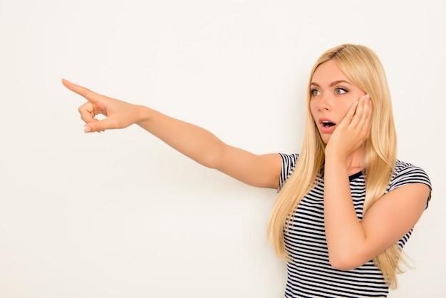 Blonde choquée touchant son visage et pointant du doigt