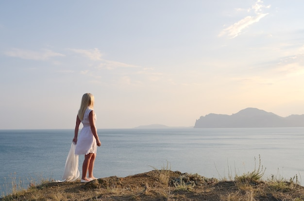 Blonde dans une robe blanche debout sur la montagne et regarde la mer