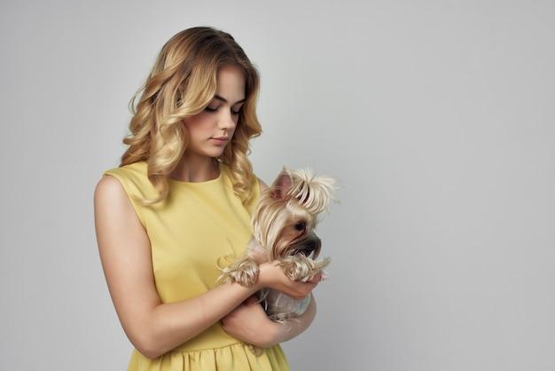 Blonde dans une robe jaune amusant un petit chien fond isolé