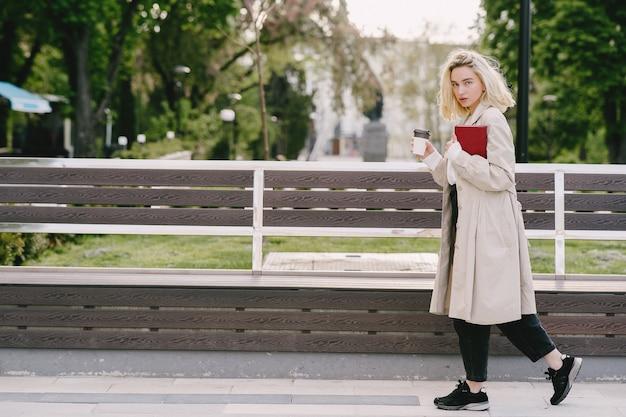 Blonde Dans Une Ville D'été Avec Une Tasse De Café Photo gratuit