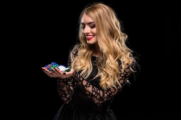 Blonde élégante dans une robe noire, joueur de casino tenant une poignée de jetons sur fond noir