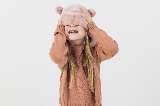 Blonde enfant couvrant son visage avec chapeau d'hiver