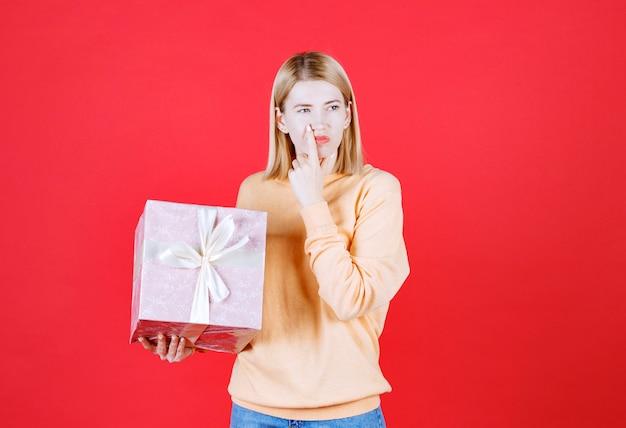Blonde femelle met sa main près de sa bouche tout en tenant la boîte-cadeau devant le mur rouge