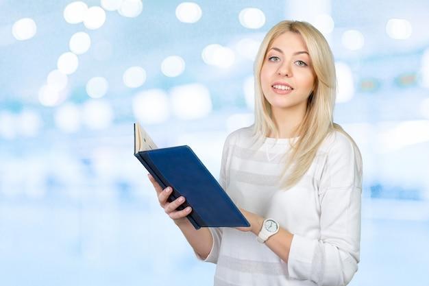 Blonde femme d'affaires écrit des notes dans le presse-papiers