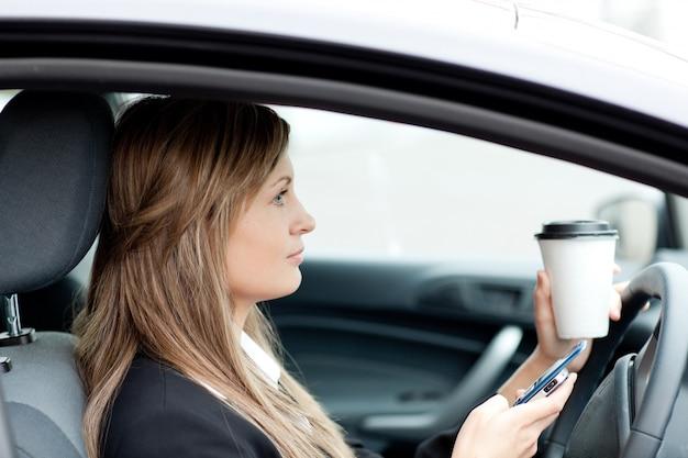 Blonde femme d'affaires envoie un texte en conduisant
