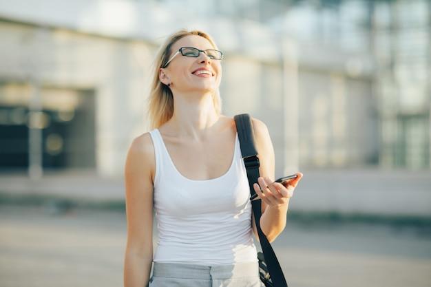 Blonde femme d'affaires lit un message sur le téléphone