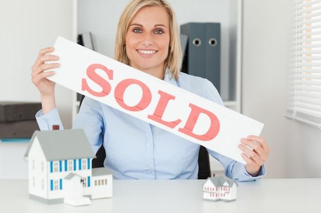 Blonde femme d'affaires montrant vendu signe regardant dans la caméra
