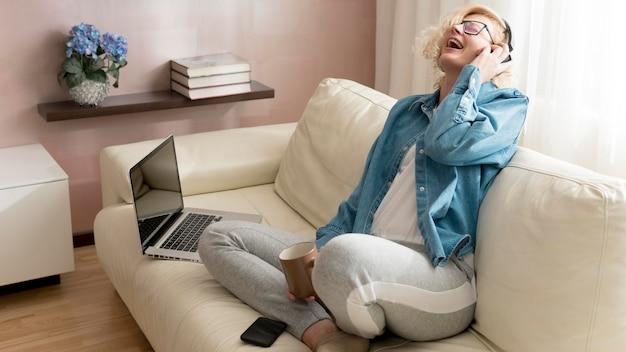 Blonde femme écoutant de la musique et tenant une tasse de café