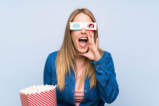 Blonde femme mangeant des popcorns criant avec la bouche grande ouverte