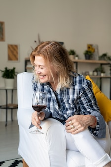 Blonde femme mature en riant en chemise à carreaux et jeans blancs assis dans un fauteuil en cuir et ayant un verre de vin rouge dans le salon