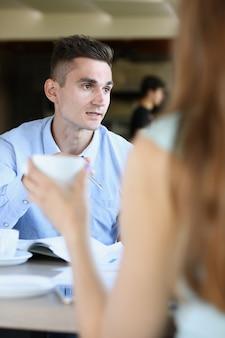 Blonde femme parlant à des amis dans un café