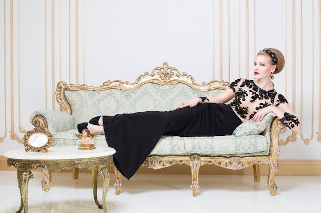 Blonde femme royale sur un canapé rétro dans une magnifique robe de luxe avec un verre de vin à la main. intérieur. espace copie