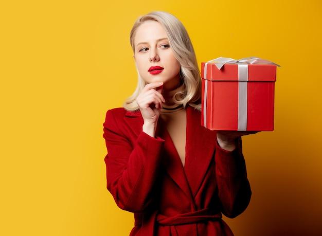 Blonde femme surprise en manteau rouge avec boîte-cadeau sur mur jaune