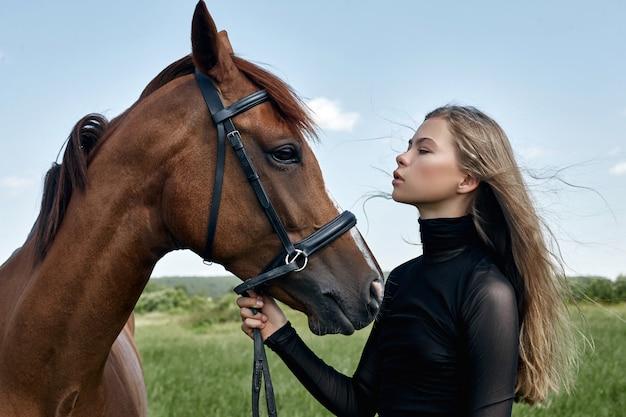 Blonde femme tenant un cheval par la bride
