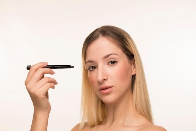 Blonde femme tenant un eye-liner près du visage