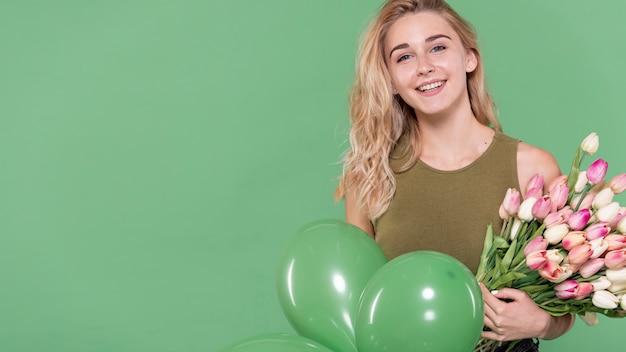 Blonde femme tenant des fleurs et des ballons