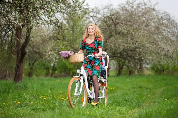 Blonde femme à vélo de ville avec bébé dans une chaise de vélo
