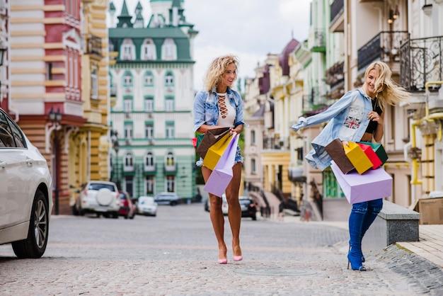 Blonde filles avec des sacs à provisions sur la rue