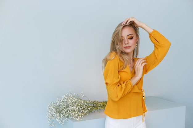 Blonde sur un fond élégant avec des cheveux sains et un maquillage d'automne