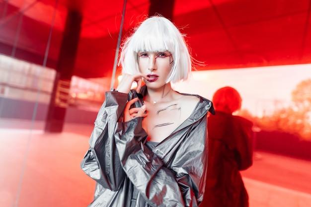 Blonde futuriste élégante dans un style cyberpunk sur un miroir rouge.