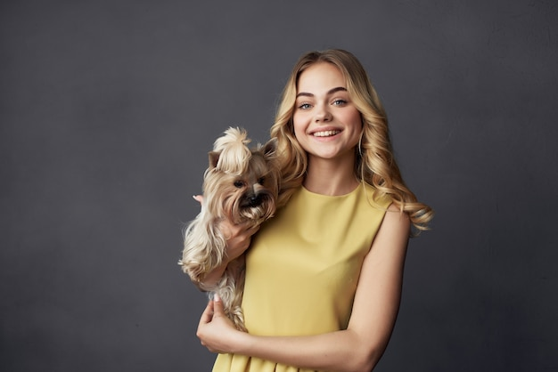 Blonde gaie dans une robe jaune petit amusement de chien de race