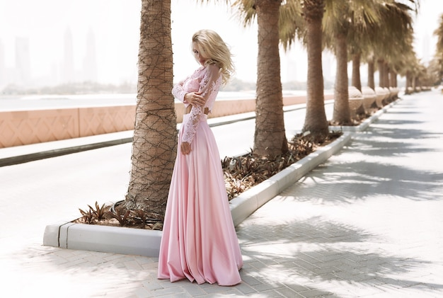 Blonde galbée au bord de la mer à dubaï, palmiers, robes chaudes et magnifiques, tir de mode de mode de vie ensoleillé d'été, agitant la robe du vent, calme et se détendre près de la piscine, coiffure, maquillage