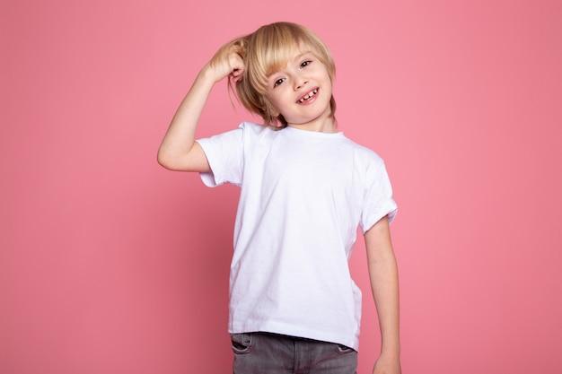 Blonde garçon souriant en t-shirt blanc et jeans gris sur mur rose