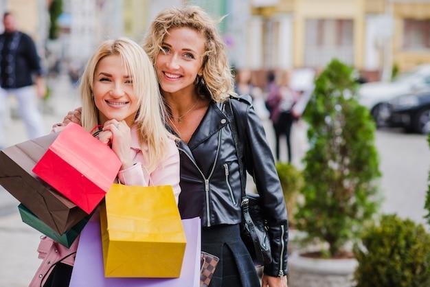 Blonde girls debout à l'extérieur en souriant