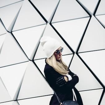 Blonde glamour debout au mur. style de mode urbain noir et blanc