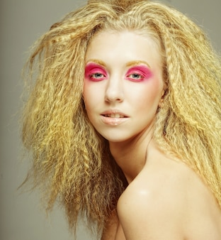 Blonde heureuse avec du maquillage rose