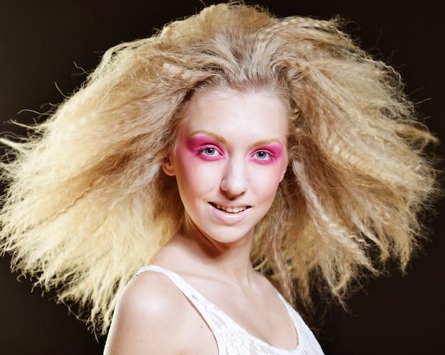 Blonde heureuse avec maquillage rose