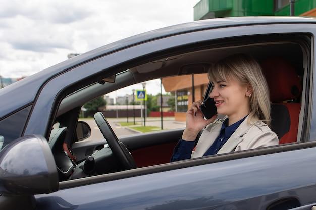La blonde heureuse parle au téléphone dans la voiture
