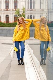 Blonde en imperméable jaune avec sac écologique en ville par temps de pluie