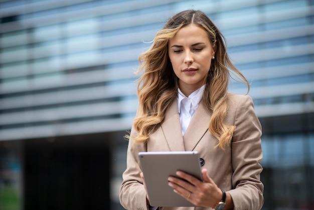 Blonde jeune femme d'affaires à l'aide d'une tablette numérique en plein air
