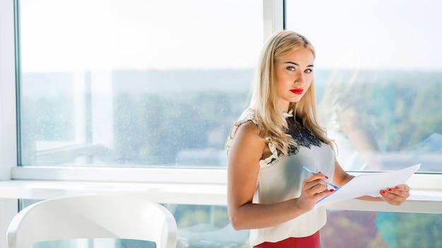Blonde jeune femme d'affaires détenant un document dans le bureau