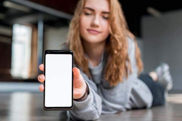 Blonde jeune femme allongée sur le sol montrant un téléphone portable avec écran blanc